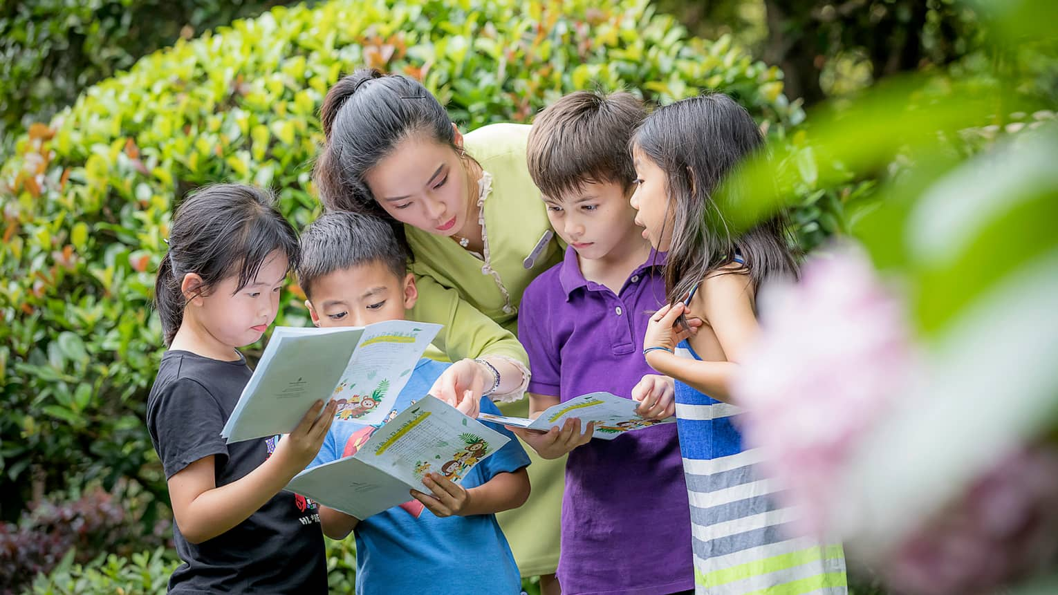 Children gather around hotel staff with treasure hunt kids activity pamphlets