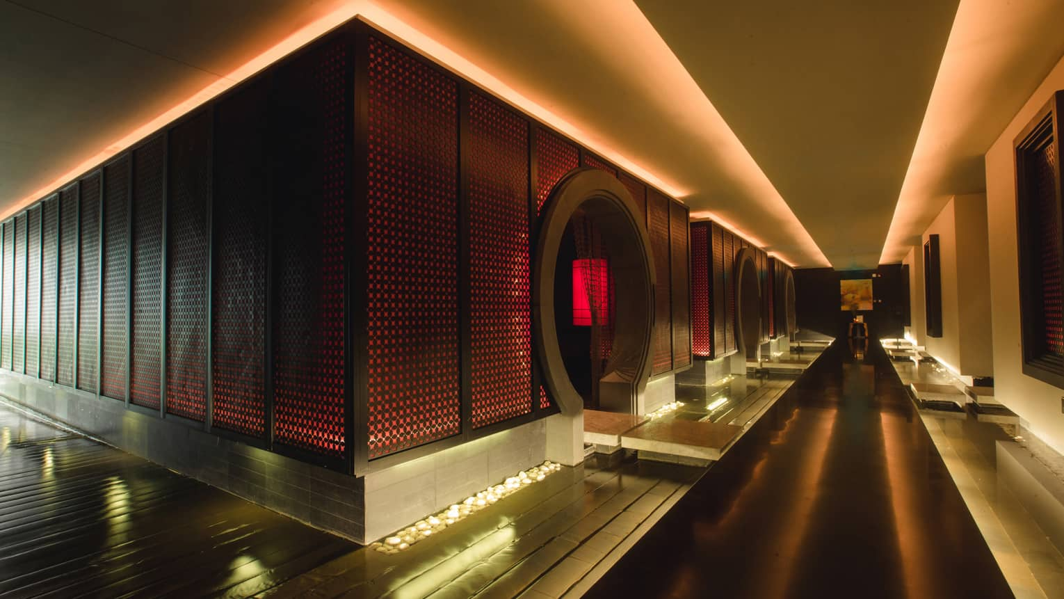 Dark floating walkway down dramatic spa hall past wall with red lights, circular doorways