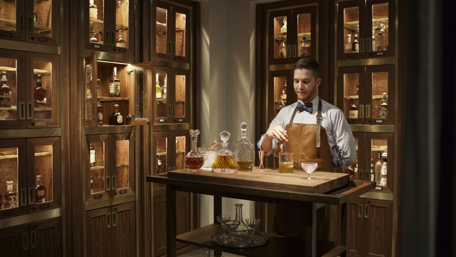 Bayou & Bottle mixologist in apron stirs bourbon cocktail, surrounded by illuminated display cases with bottles