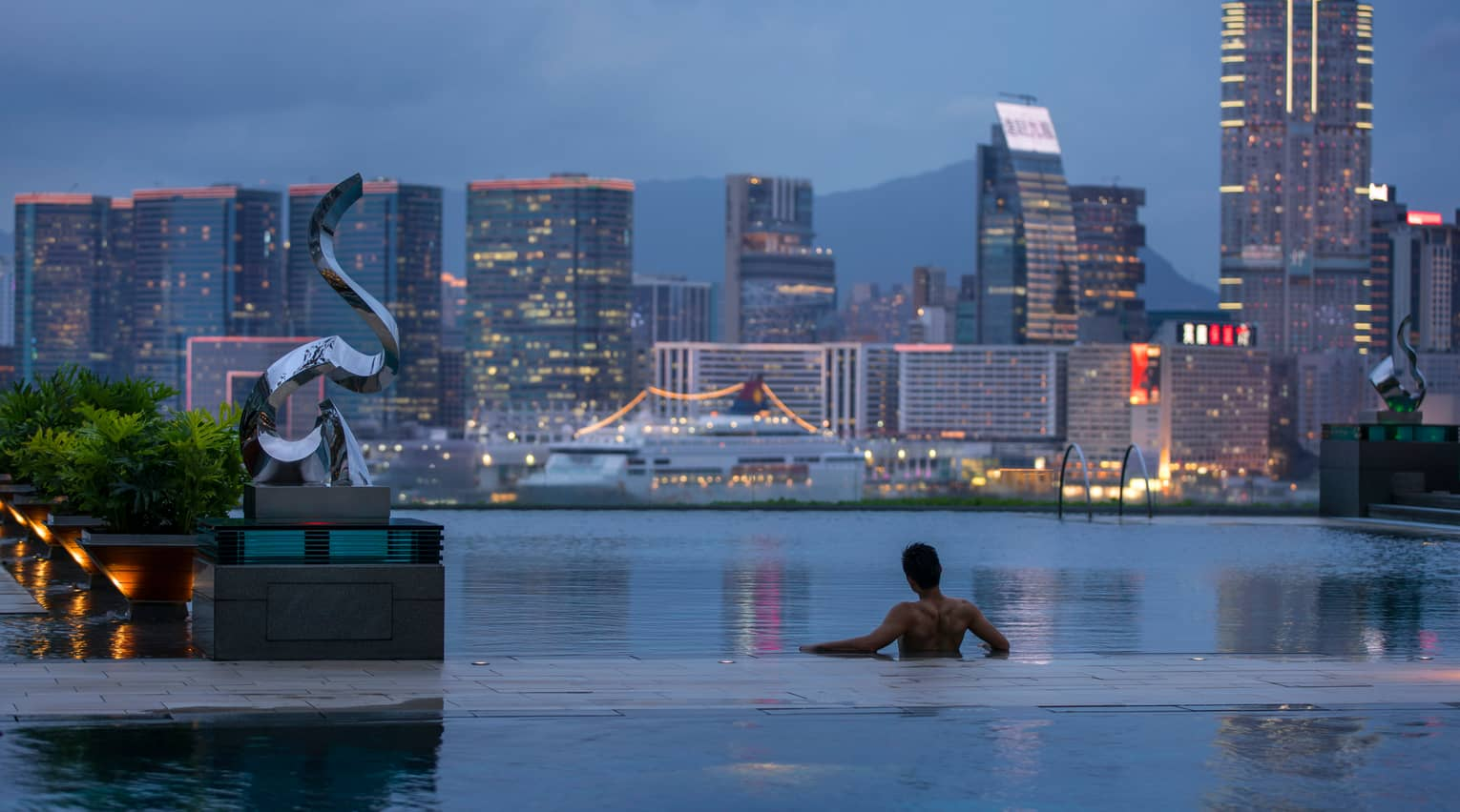 Silhouette of back of man wading in infinity swimming pool, looking out at Hong Kong harbour at dusk
