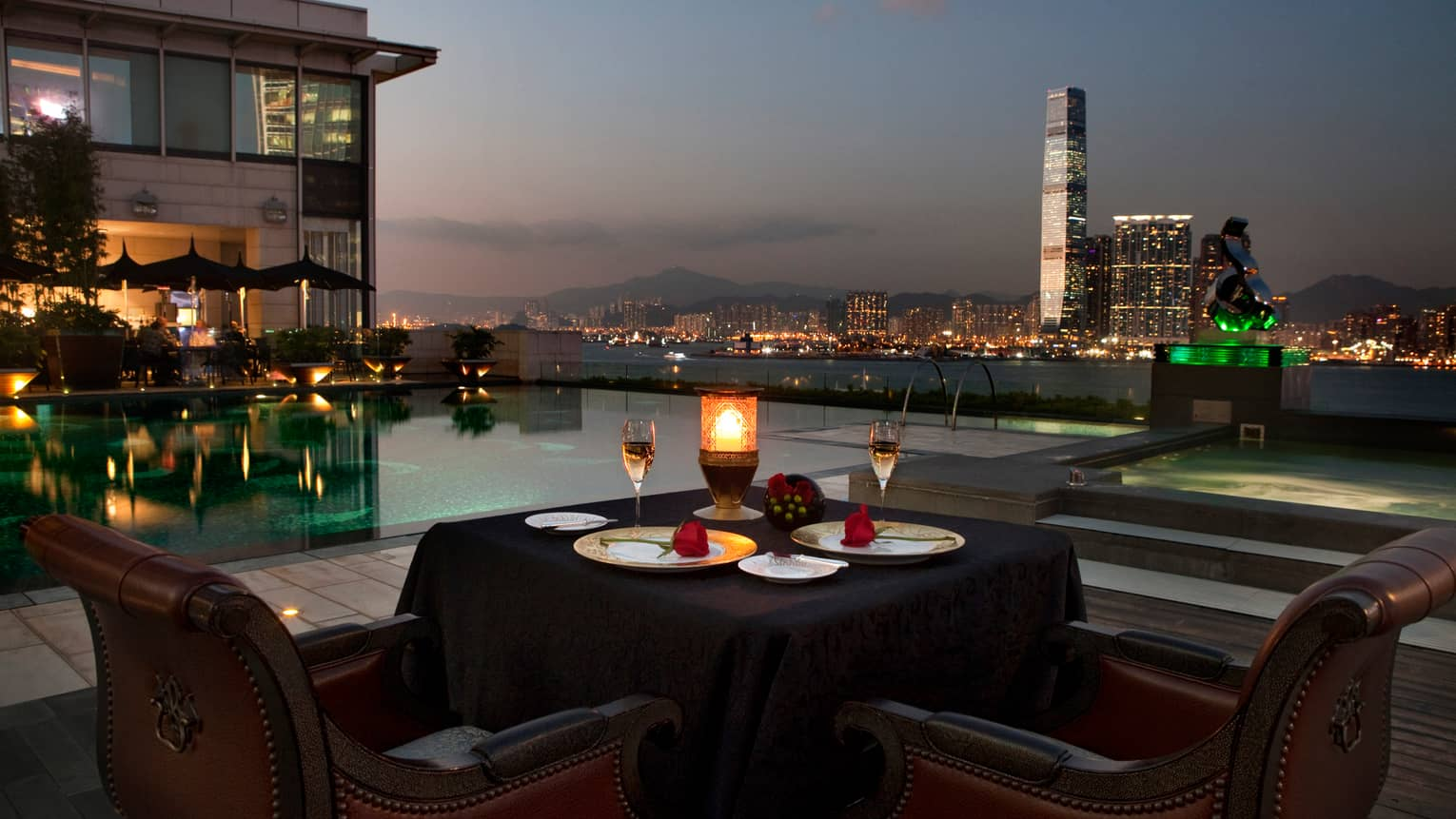 Candle-lit patio dining table by swimming pool at night, skyscrapers and city lights
