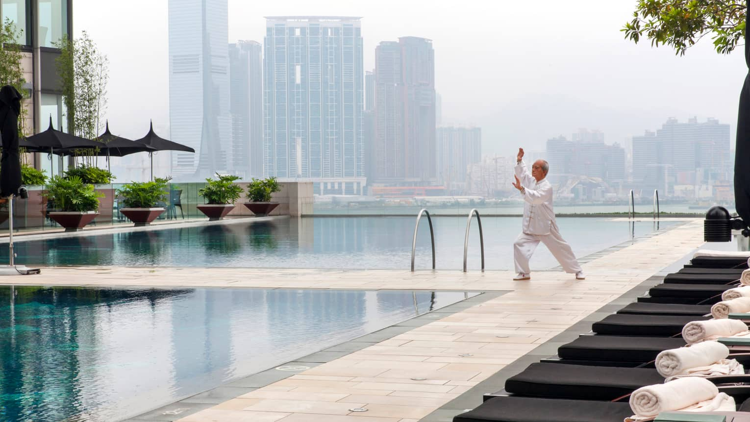 Tai Chi master wearing white holds pose on patio deck by swimming pools, misty skyline