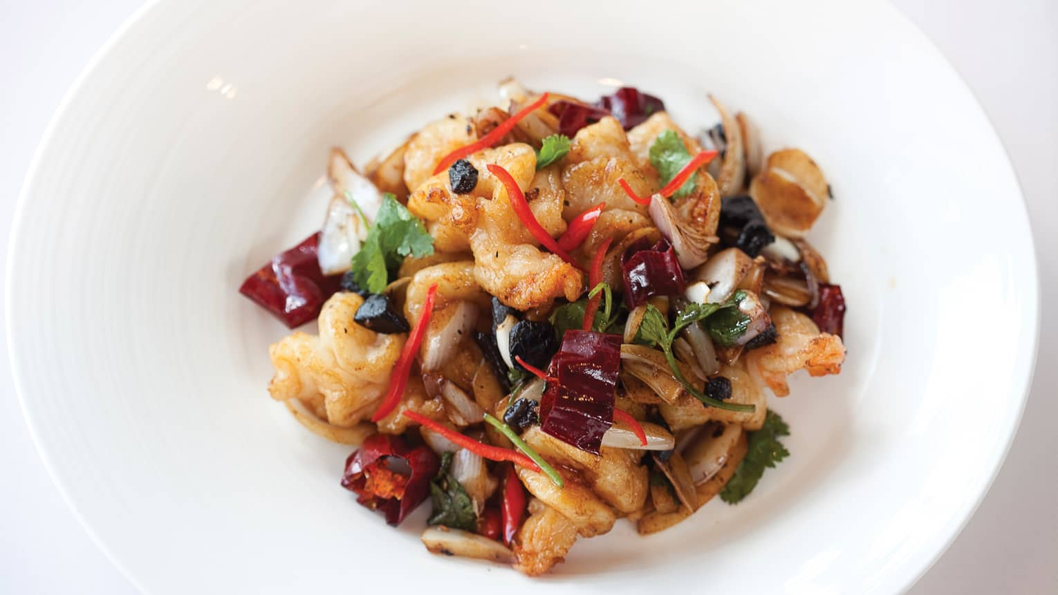 Wok-fried prawns with vegetables in white dish