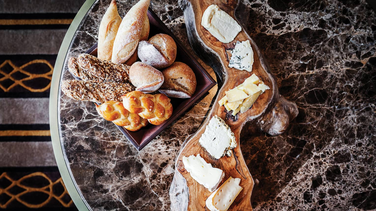 Aerial view of rustic wood platter with artisanal cheeses, breads