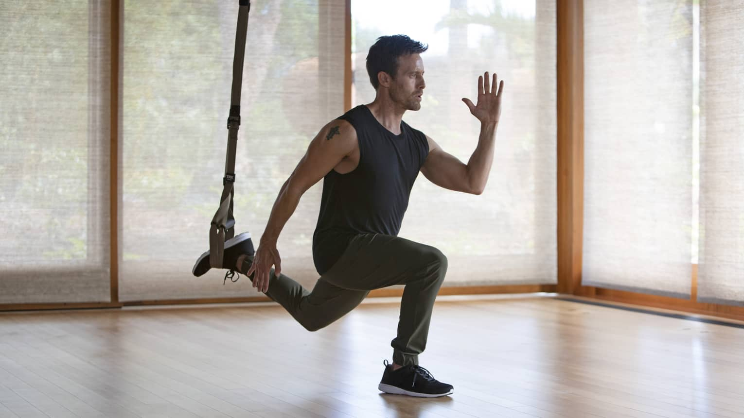 Man exercises with bungee cord in a yoga studio