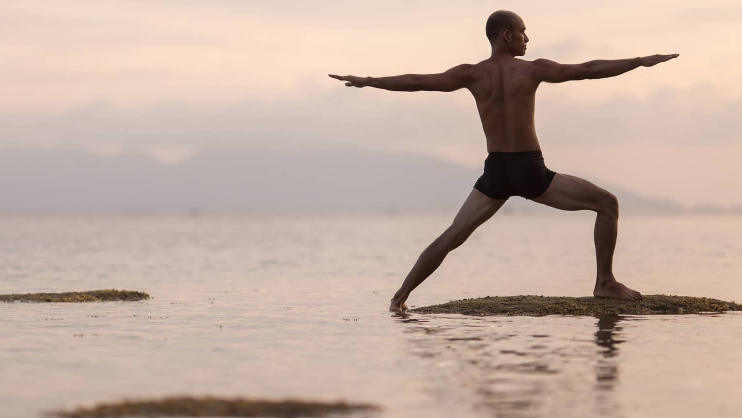 Silhouette of man in swimsuit doing yoga pose on sandbar in ocean at sunset