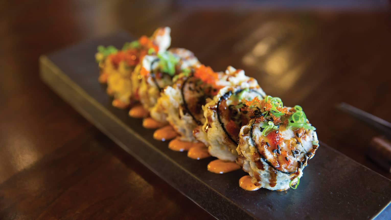Crunchy shrimp sushi rolls arranged on long tray, orange sauce