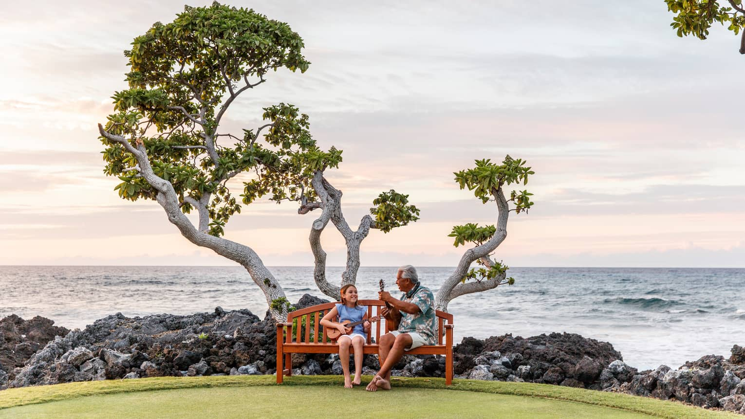 Hawaiian elder and young girl play ukuleles on bench under tree by black rocks, ocean
