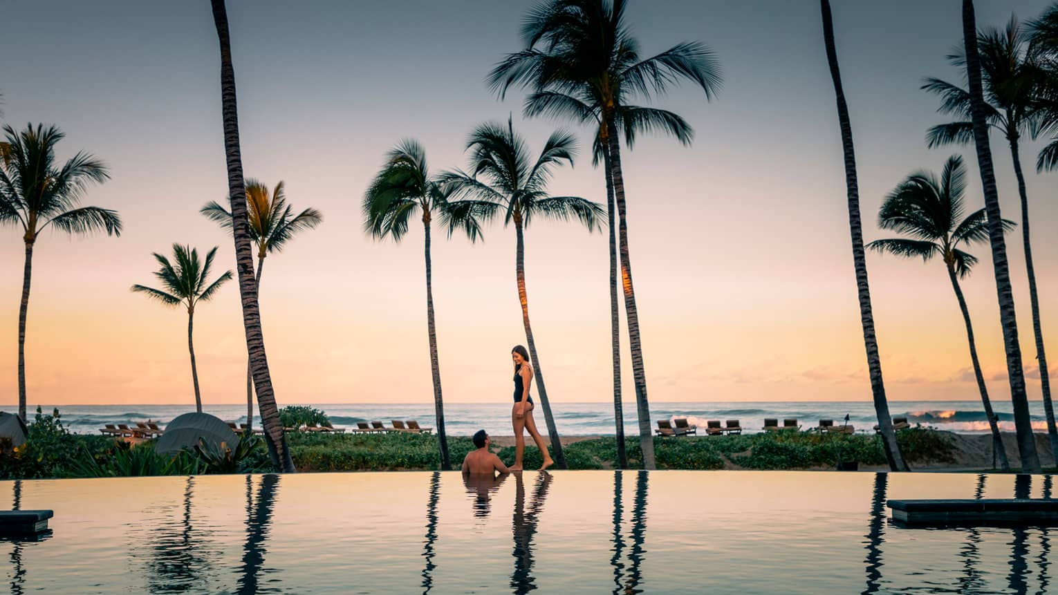 Woman in swimsuit walks on edge of pool past wading man, tall palm trees at sunset