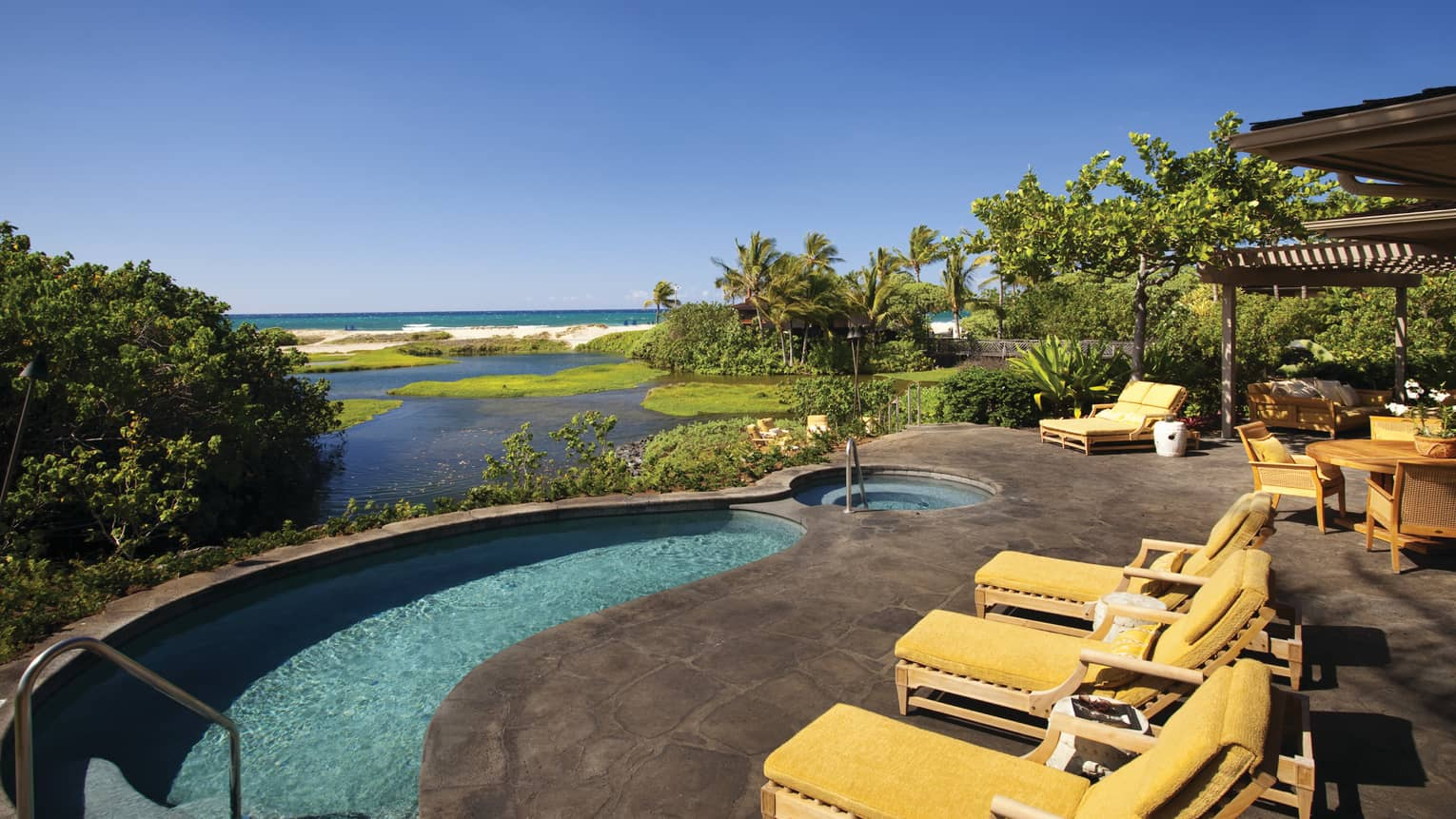 Makaloa Villa yellow patio chairs by curved plunge pool overlooking ocean, beach