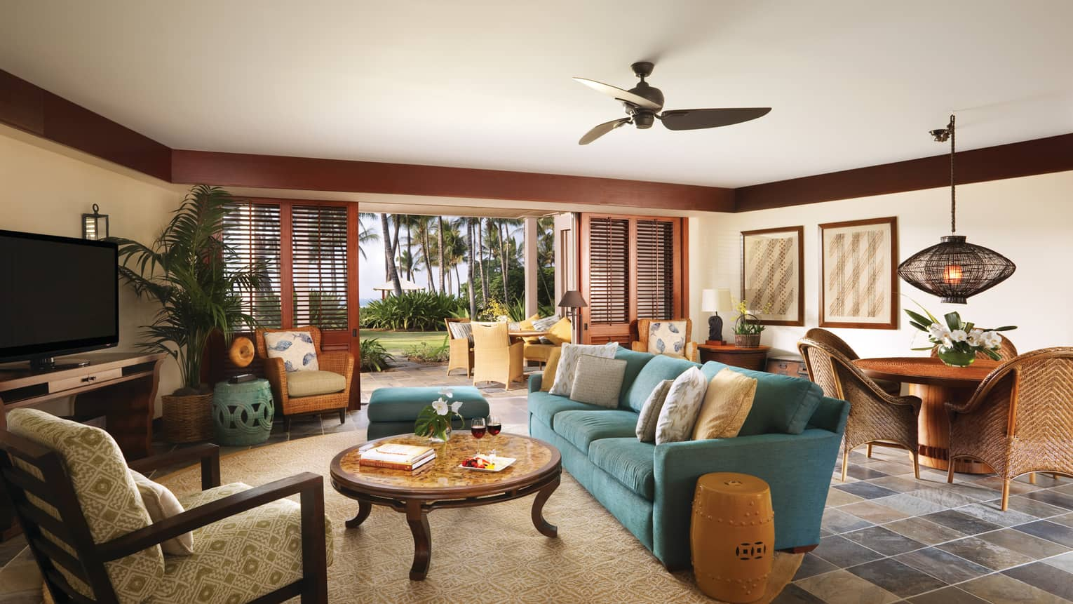Wai'olu Suite seating area on round area rug, table by open wood patio shutters