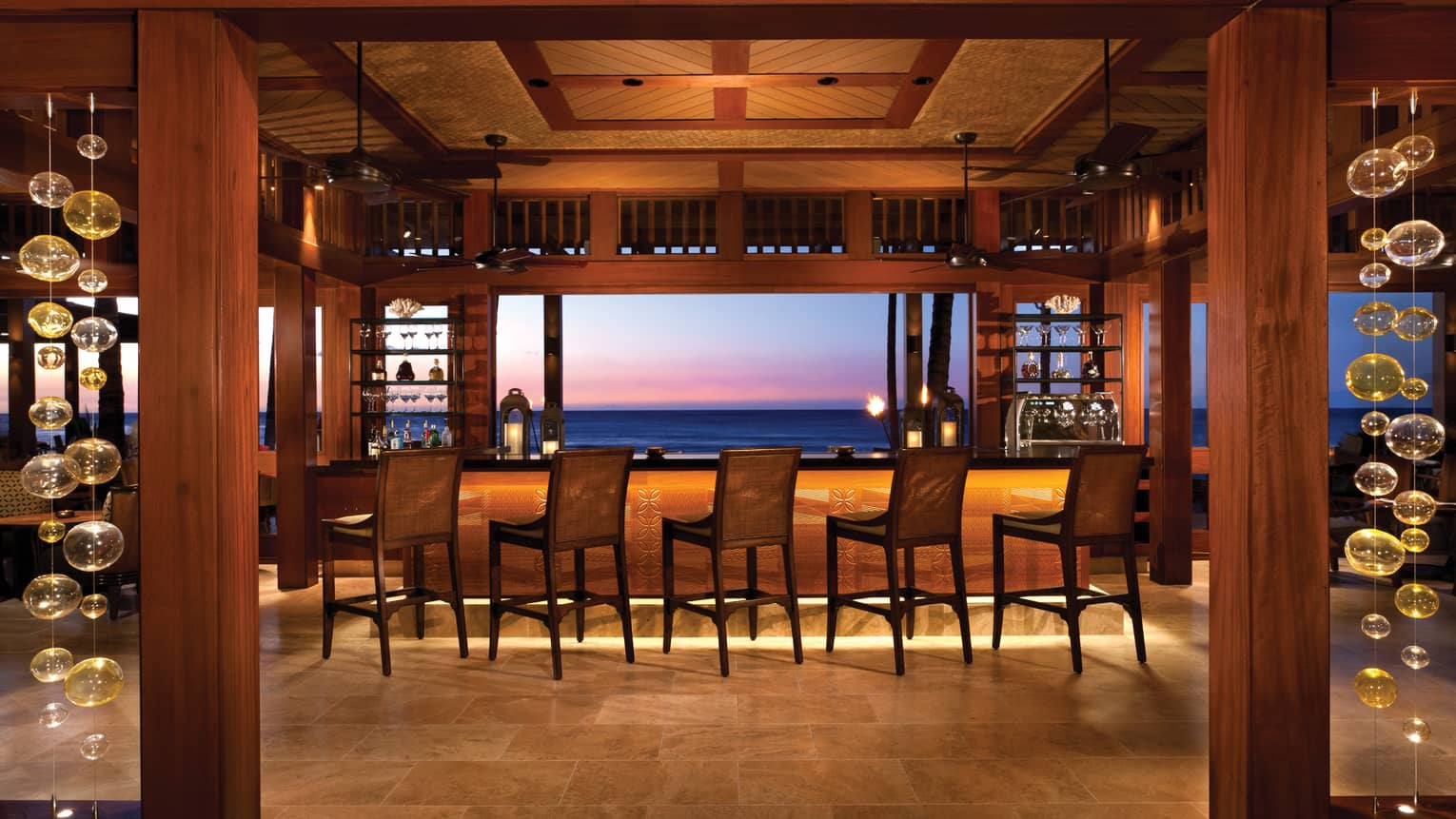 Stools along bar in ULU Sushi Lounge dining room, sunset views