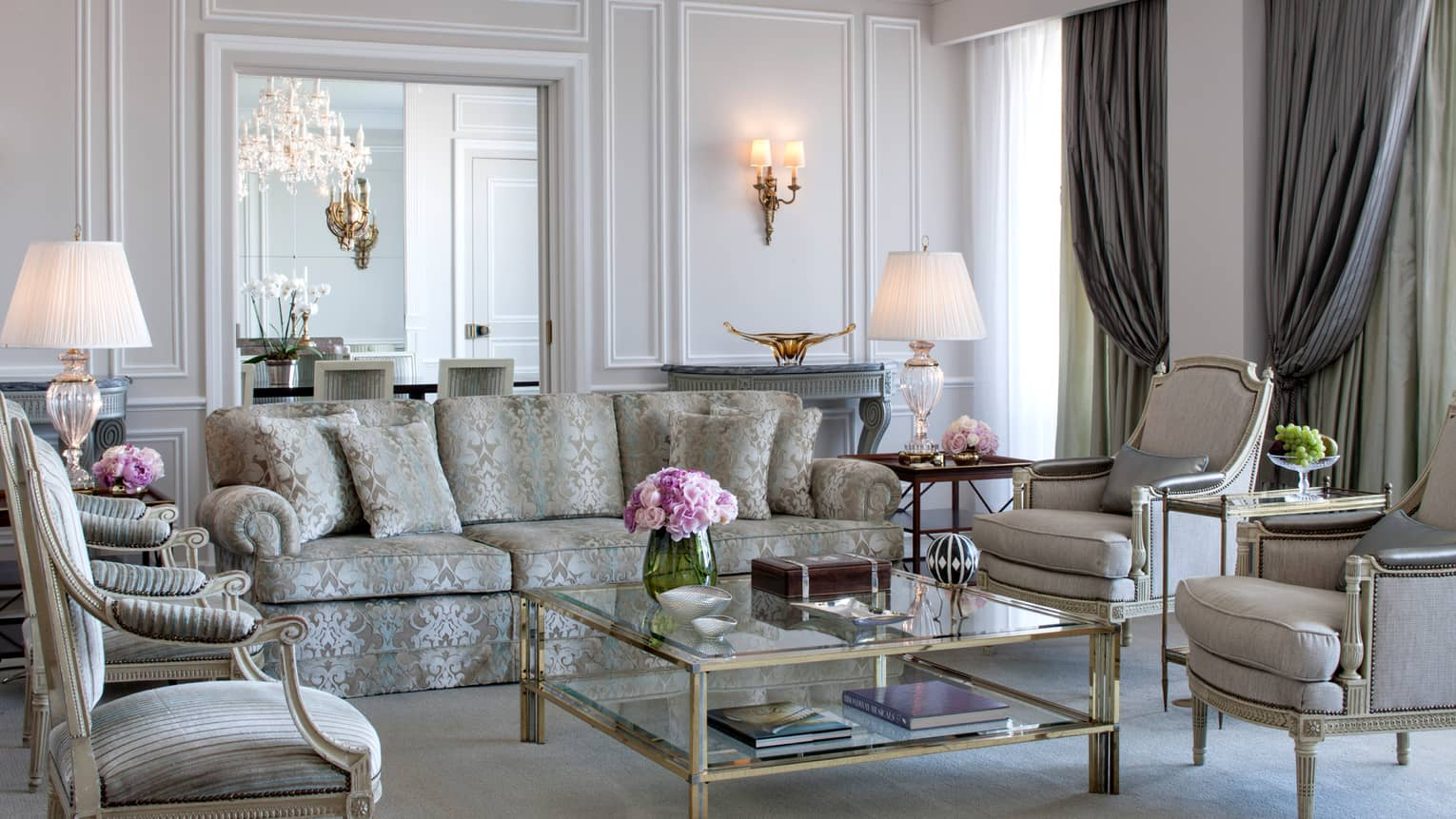 Royal Suite bright, elegant living room with blue-and-grey satin sofa, armchairs, glass coffee table with gold trim, white walls