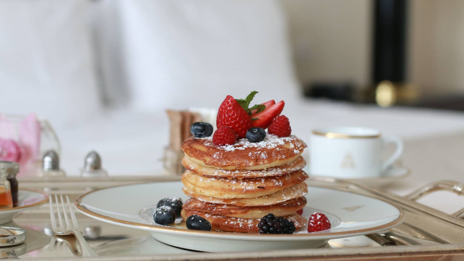 Stack of thick pancakes on plate with dusted icing sugar, fresh berries