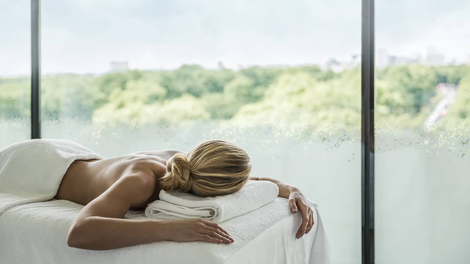 Woman lying face-down on massage table in front of sunny window