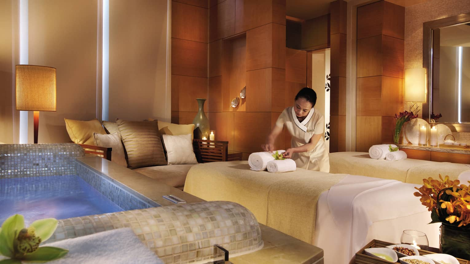 Spa staff sets rolled towels on massage bed near small sofa, tile bathtub in Couples Suite