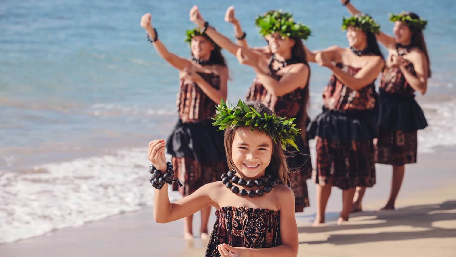 Hula dancing, smiling young girl, group of women behind her on beach, wearing traditional floral crowns, dresses