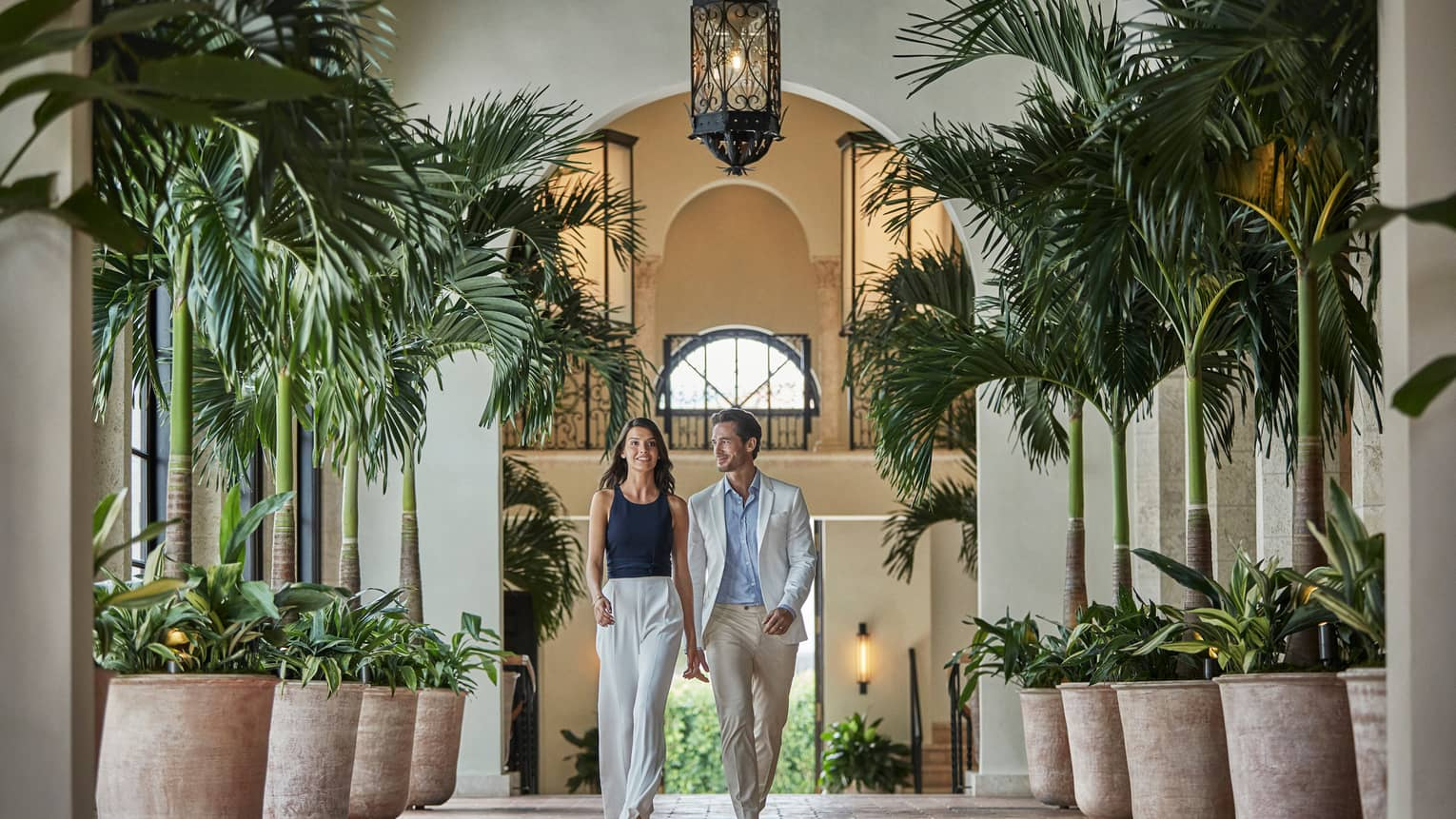 Couple walks down hallway lined with potted palm trees under arched ceiling