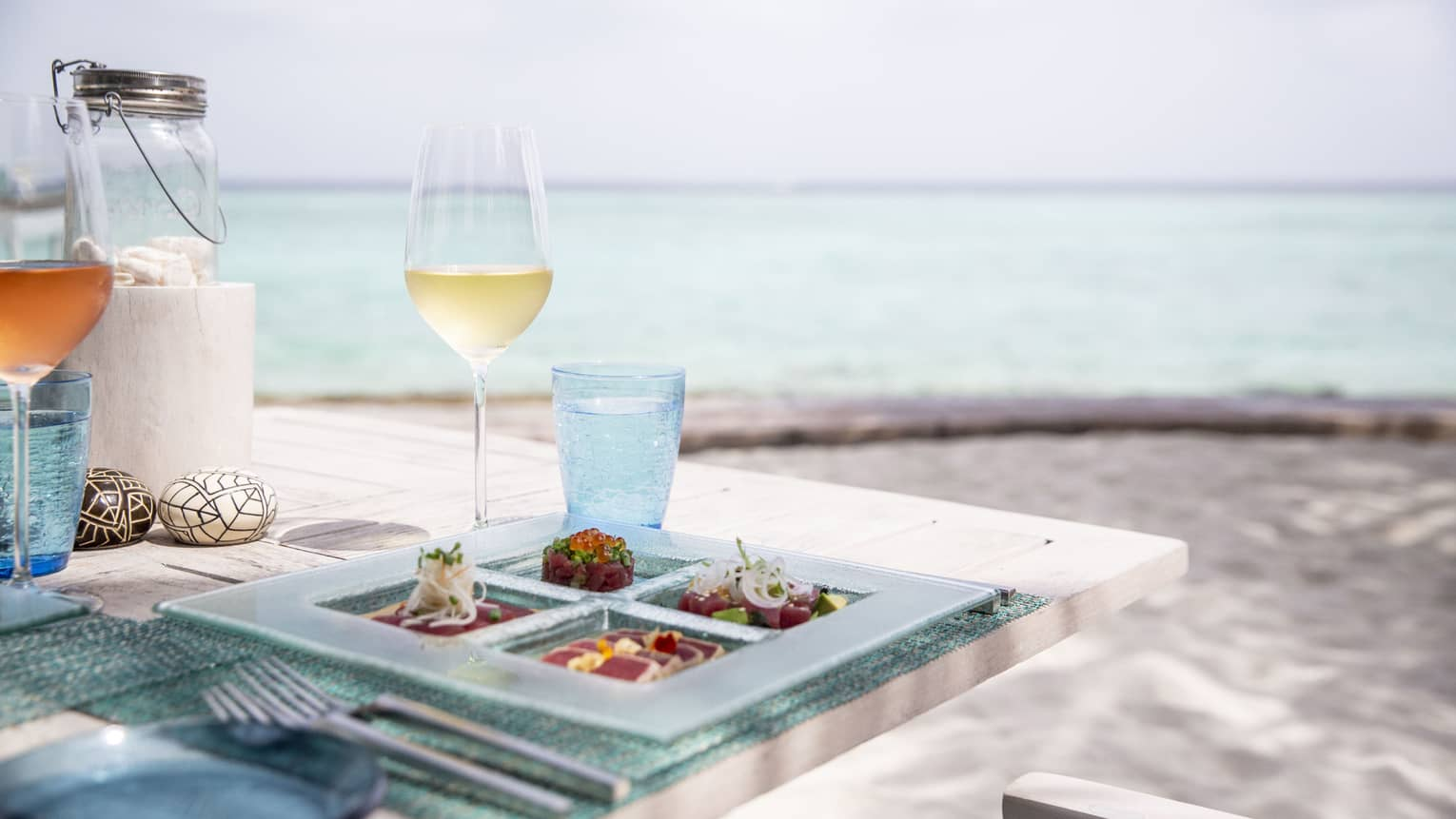 A tasetfully set table with a glass of white wine and rose overlooking the ocean at Fuego Grill