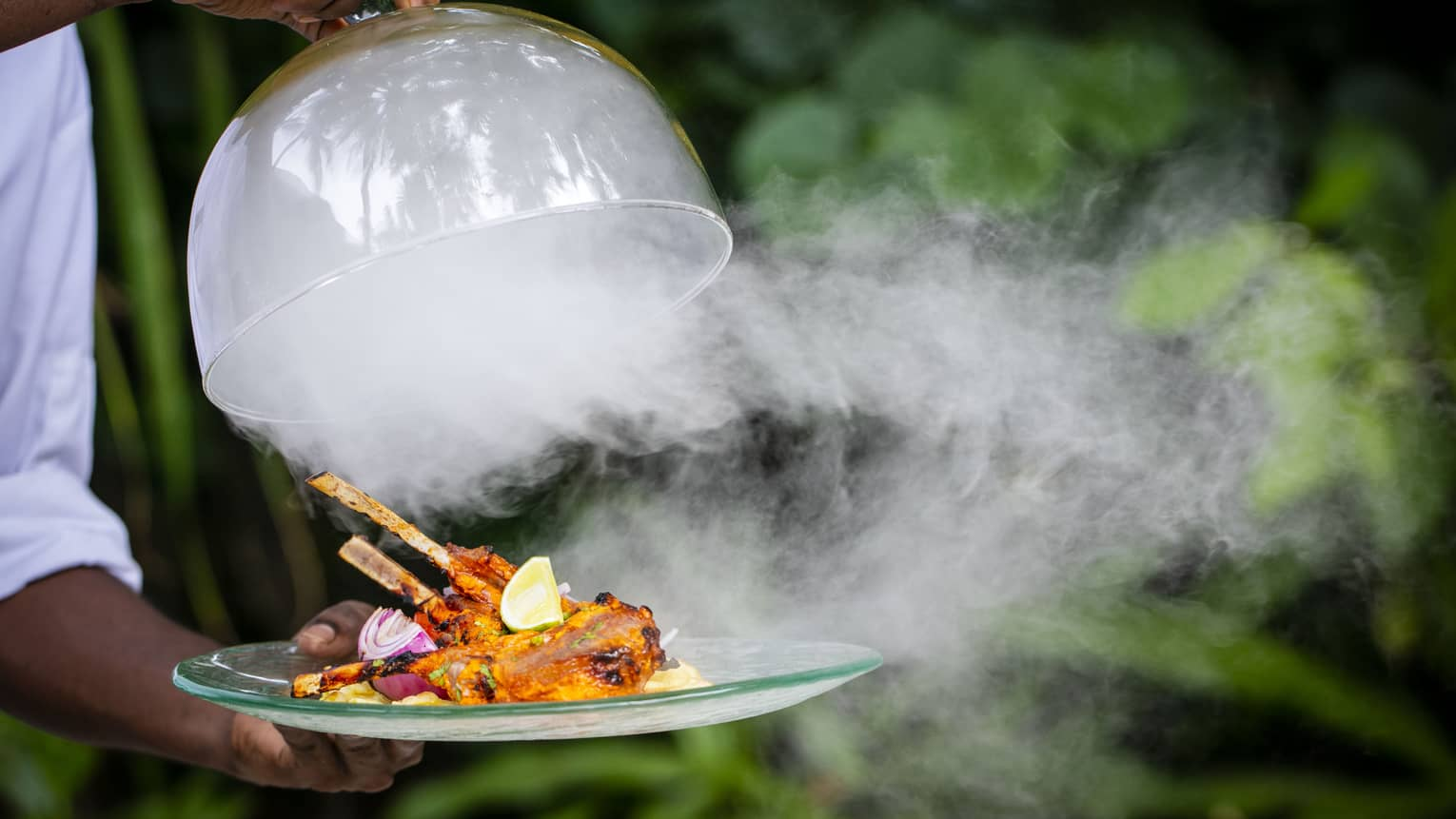 A Four Seasons dining staff taking the lid off of a dinner tray – steam is pouring out over a cooked meat dish on skewers