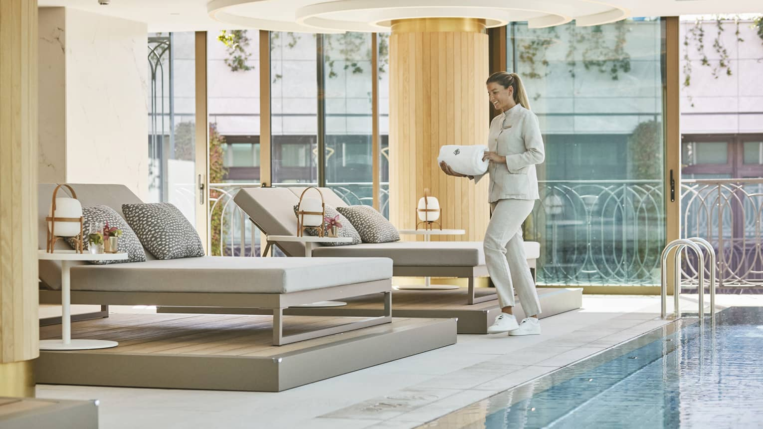A woman carrying white towels to cushioned lounge seat next to indoor pool