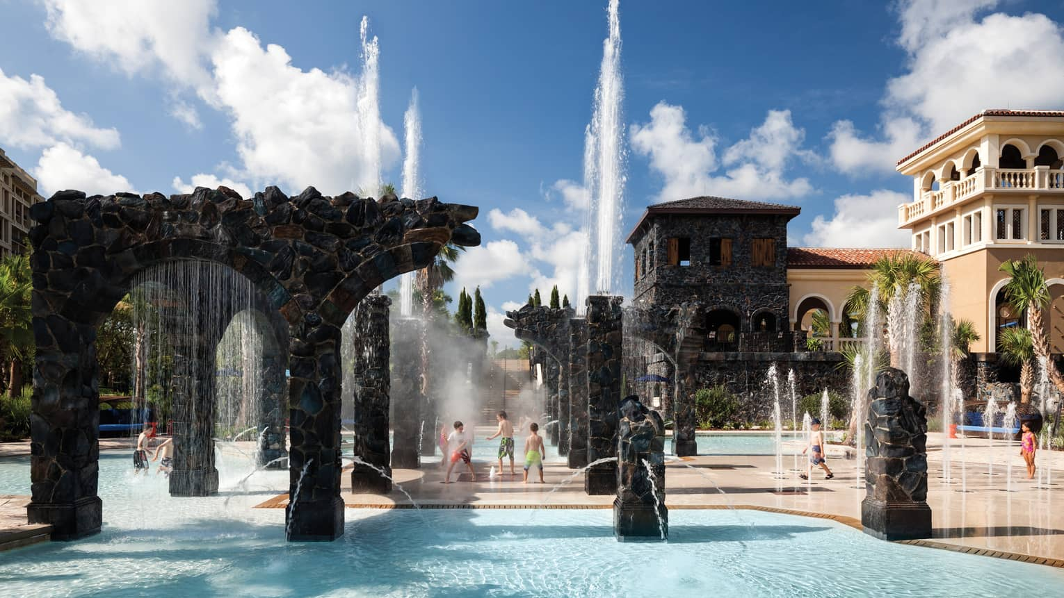 Kids play in water, under sprinklers and stone pillars in the Splash Zone water park