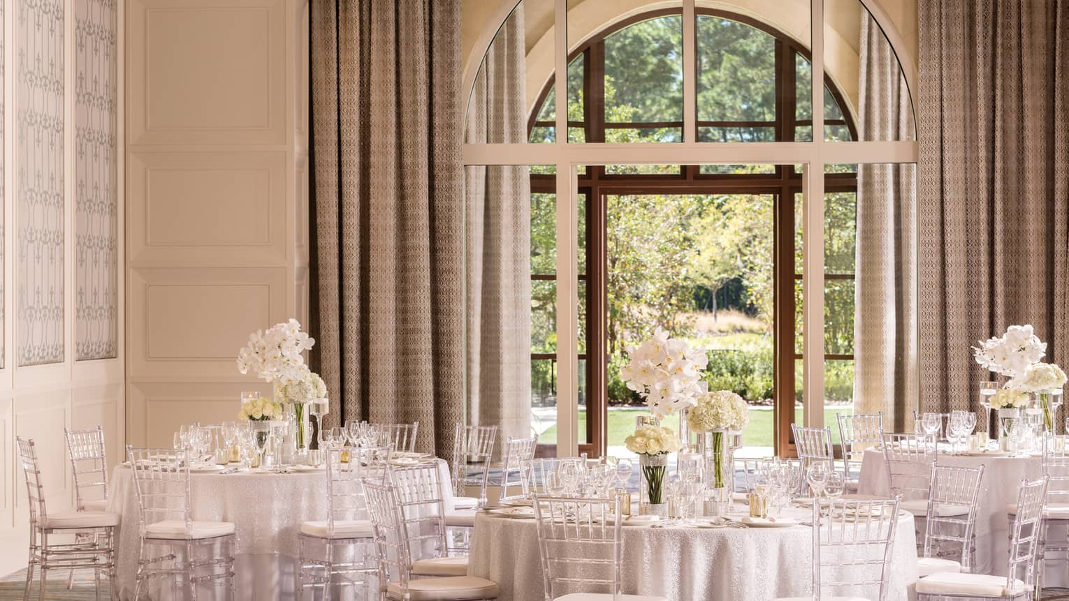 The Palm Ballroom with elegant white banquet tables under large, sunny arched window