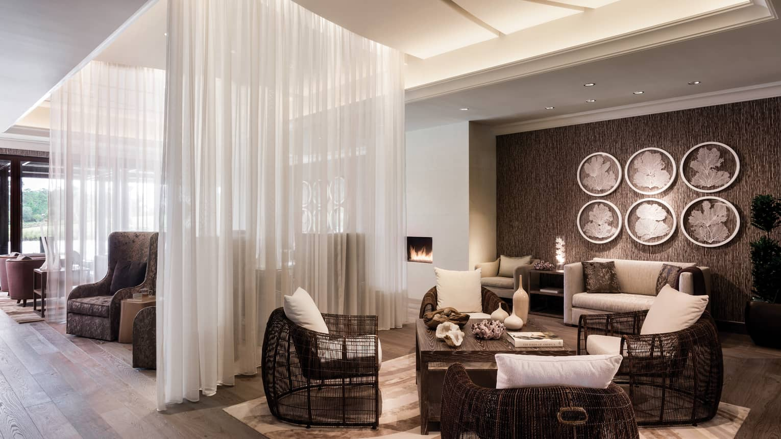 Spa lounge, wicker armchairs with white cushions, room divided by sheer white curtains