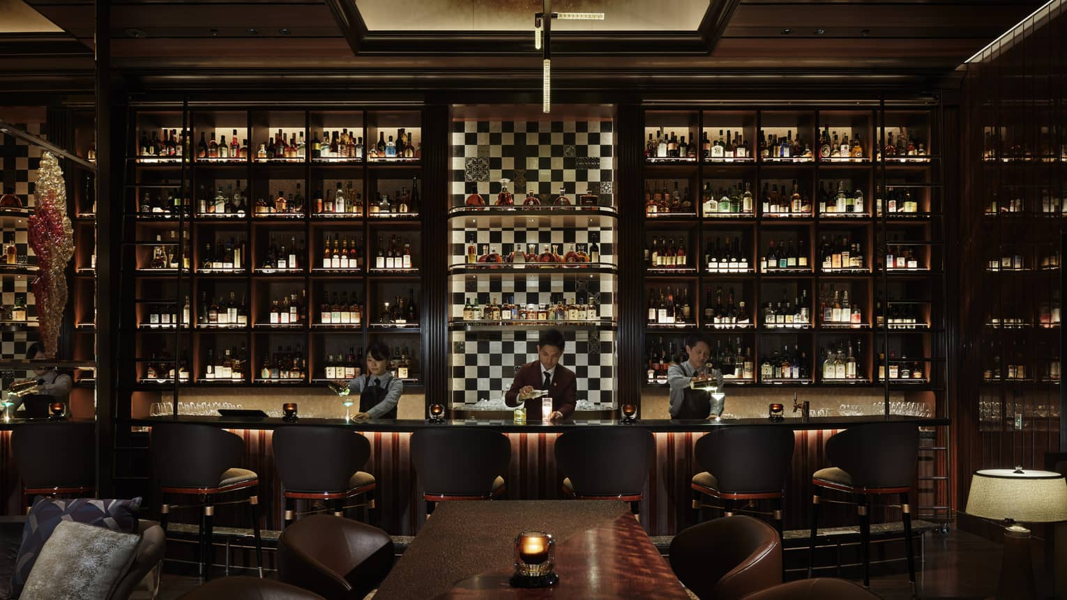 Three bartenders work behind a bar; dark wood, ceiling-height shelves span the wall