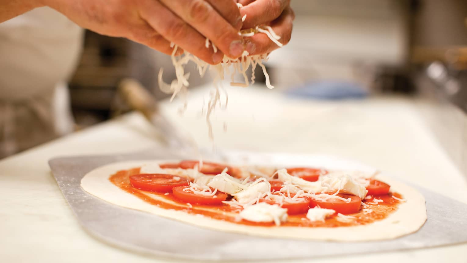 Close-up of hands sprinkling mozzarella cheese on raw personal size pizza