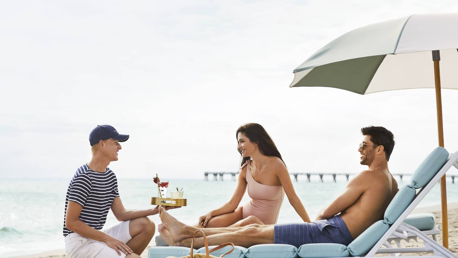 A couple receives drinks as they relax under an umbrella on the beach