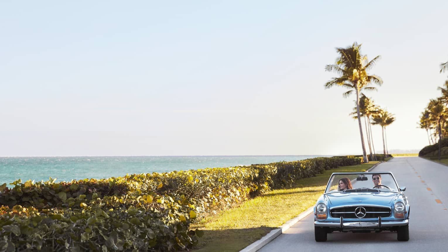 A couple drives along the shore in a blue convertible Mercedes-Benz