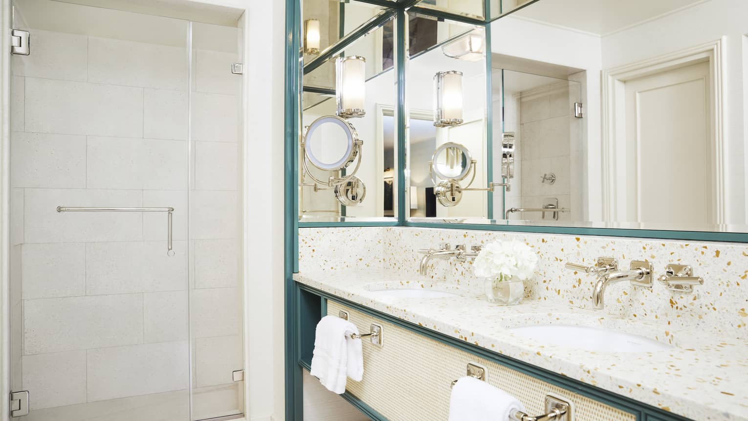 A bright bathroom has metal accents and marble countertops