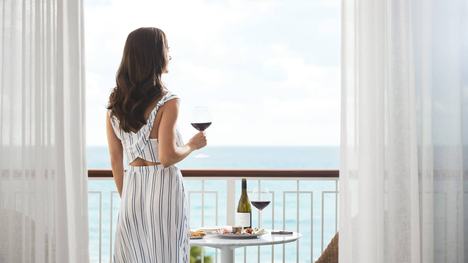 A woman enjoys a drink on the balcony of the Ocean-View Studio Suite
