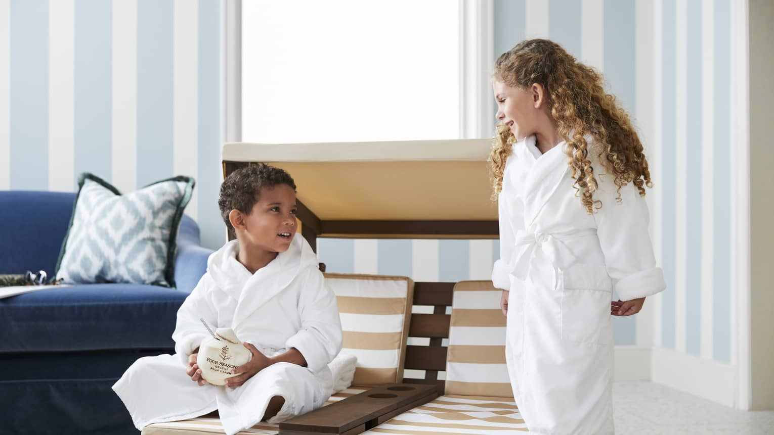 Young guests relax in white robes and enjoy a coconut beverage