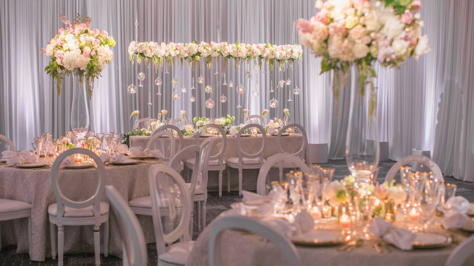 Flagler Ballroom wedding banquet with candle-lit tables, white flowers and glass bulb displays
