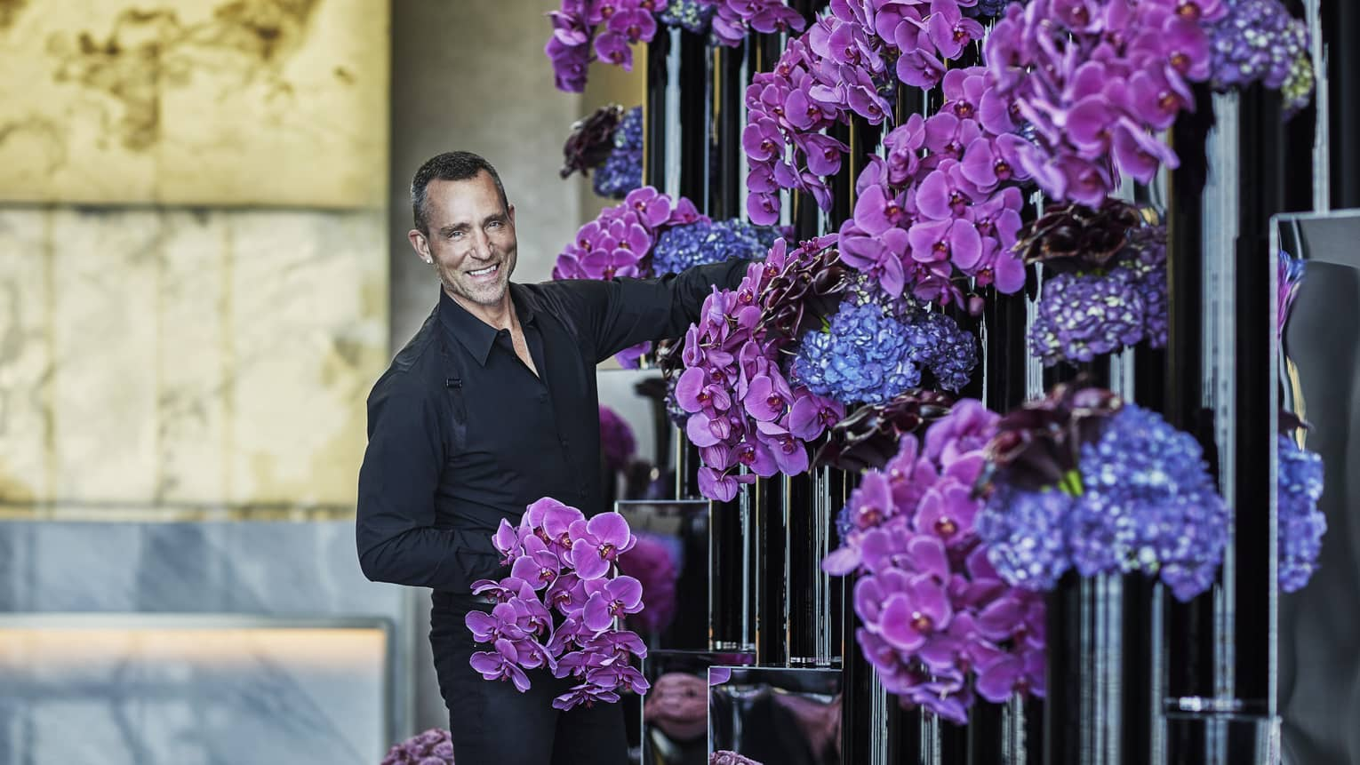 Florist arranges purple and blue flowers in tall black vases