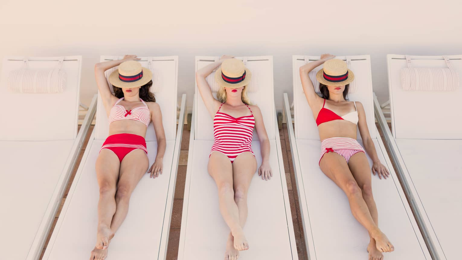 Three women in retro-style red striped bikinis lounge on pool chairs, straw fedoras over faces