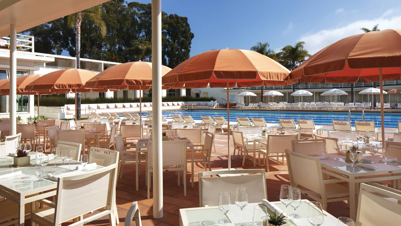 Coral Cafe and Bar patio, orange umbrellas over white dining tables, chairs by pool