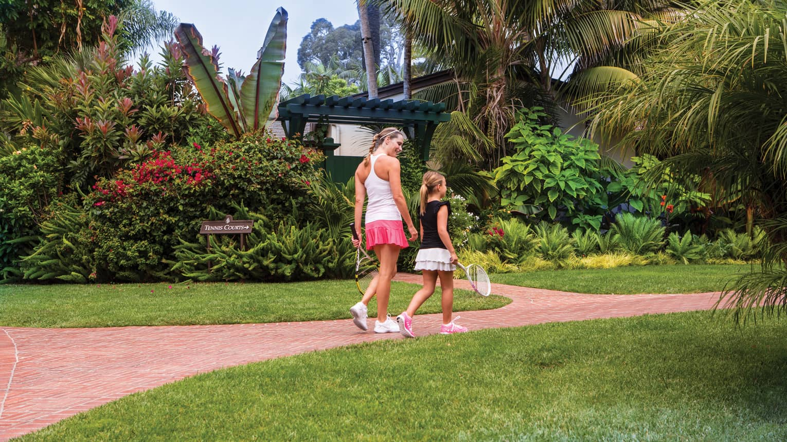 Woman and young girl holding tennis rackets walk down brick path, tropical garden