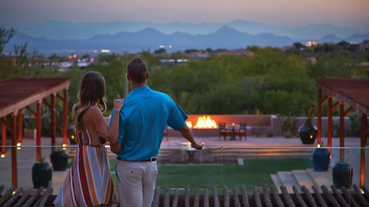 Couple stands at glass balcony overlooking hotel patio, fire pits
