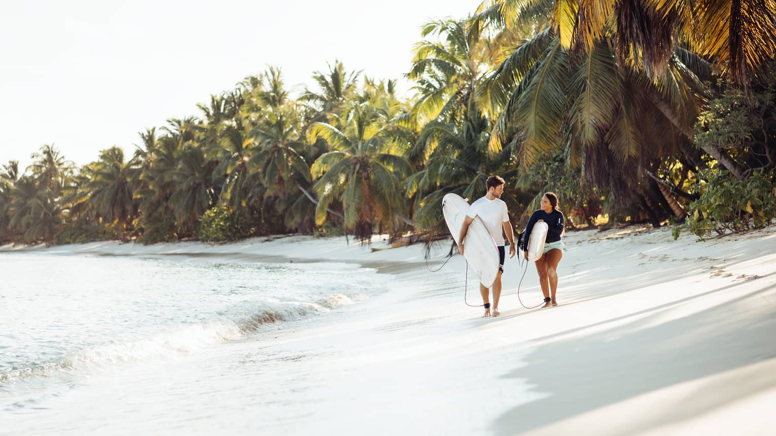 Couple walking on the beach carrying surfboard