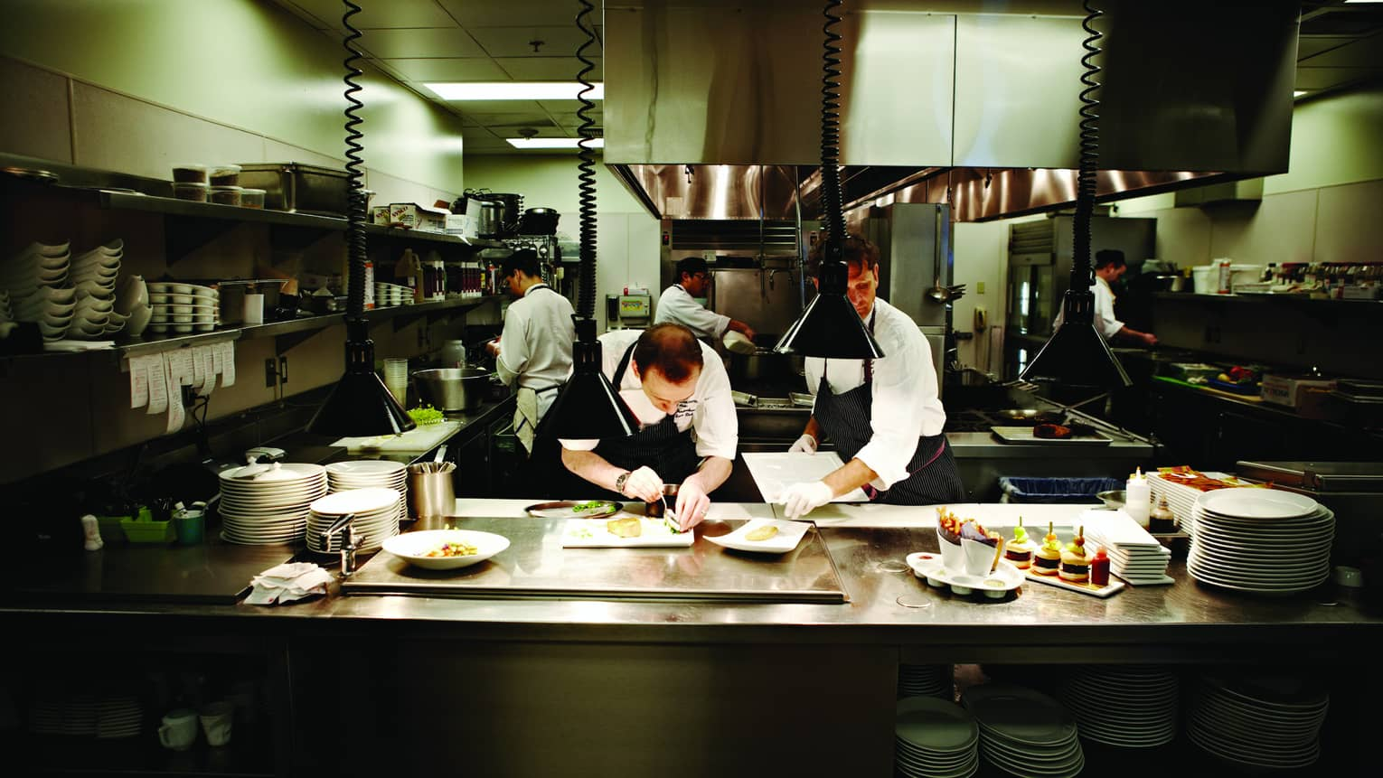 Chefs at work plating gourmet meals in stainless-steel Goldfinch Tavern kitchen