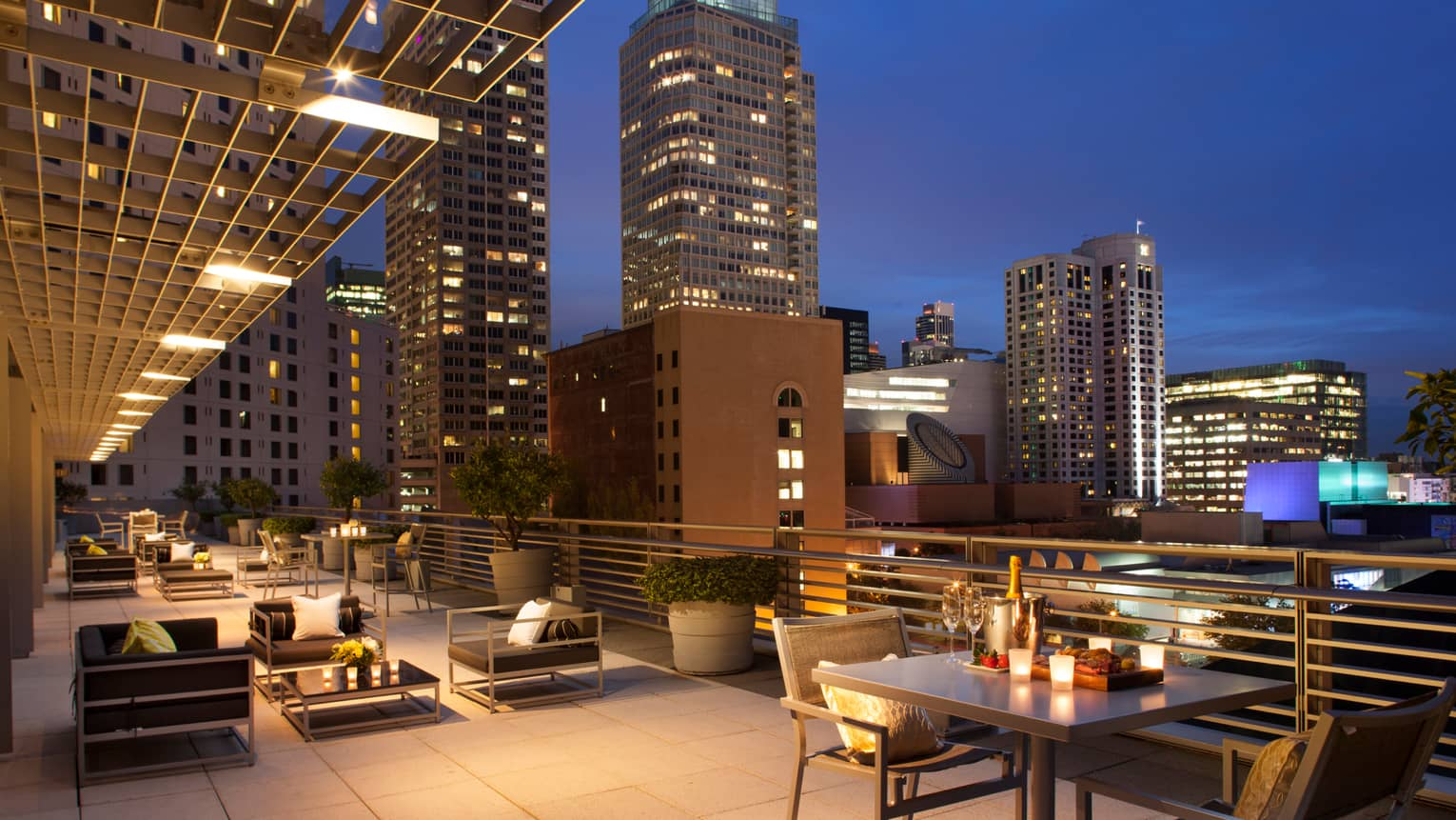 Large rooftop patio at night with candle-lit tables, champagne on ice, black cushioned chairs, city lights