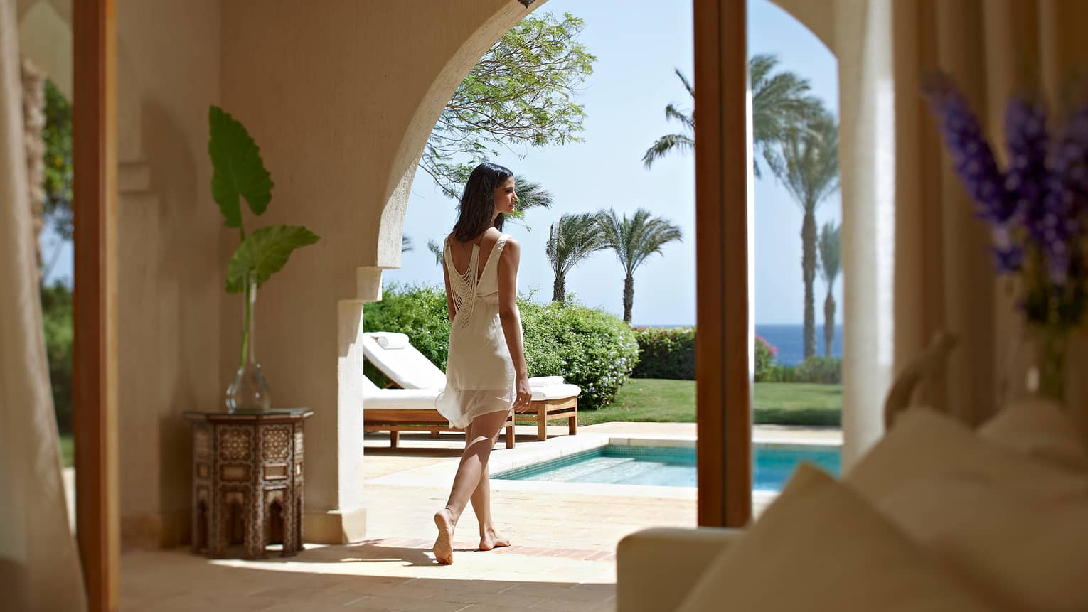 Woman wearing white dress walks through open villa door to sunny private patio, swimming pool