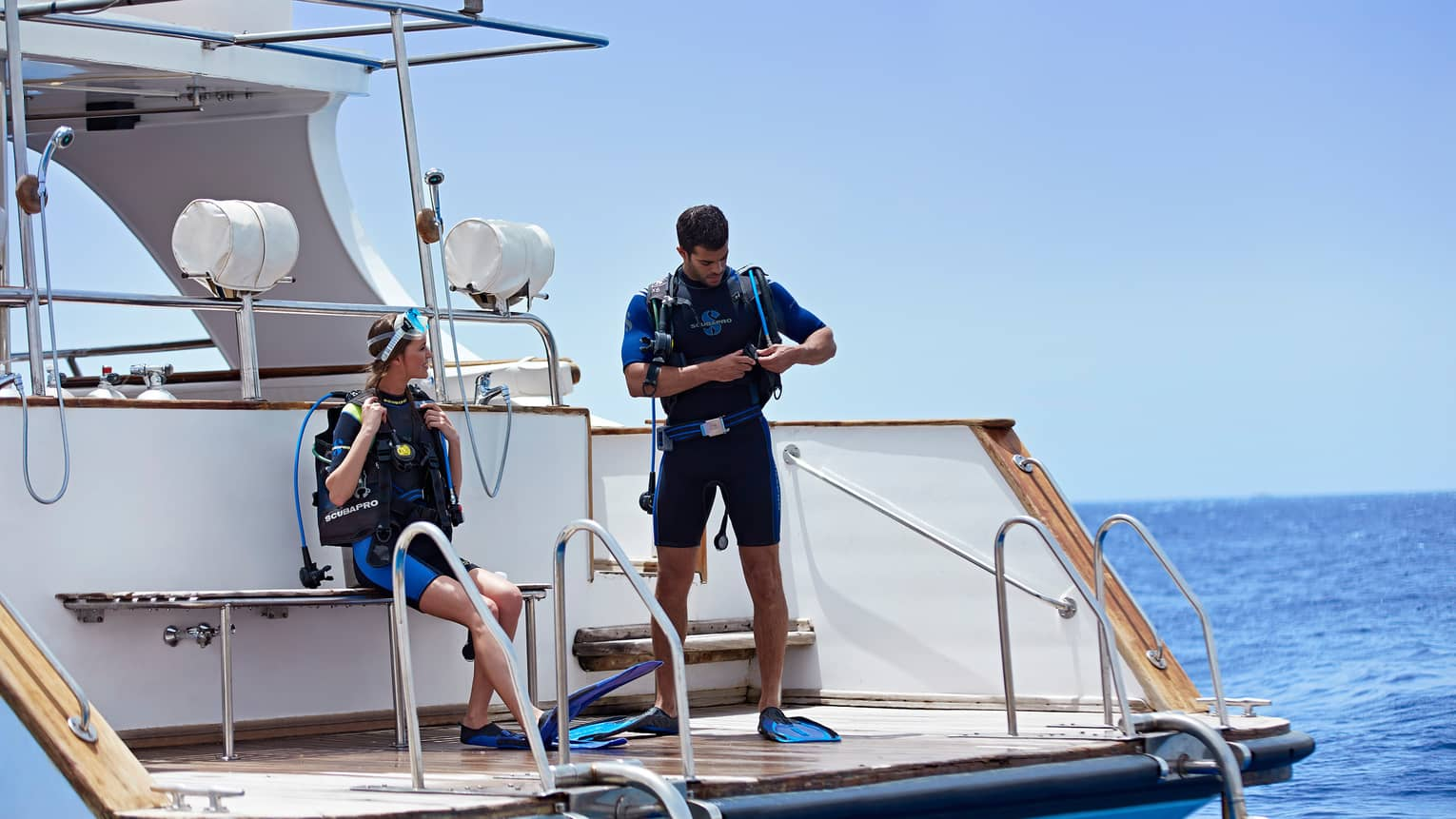 Two scuba divers in gear stand on deck of yacht