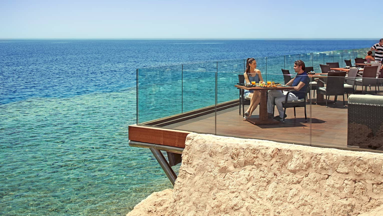 Couple dines at sunny corner patio table by glass balcony overlooking turquoise waters of Red Sea