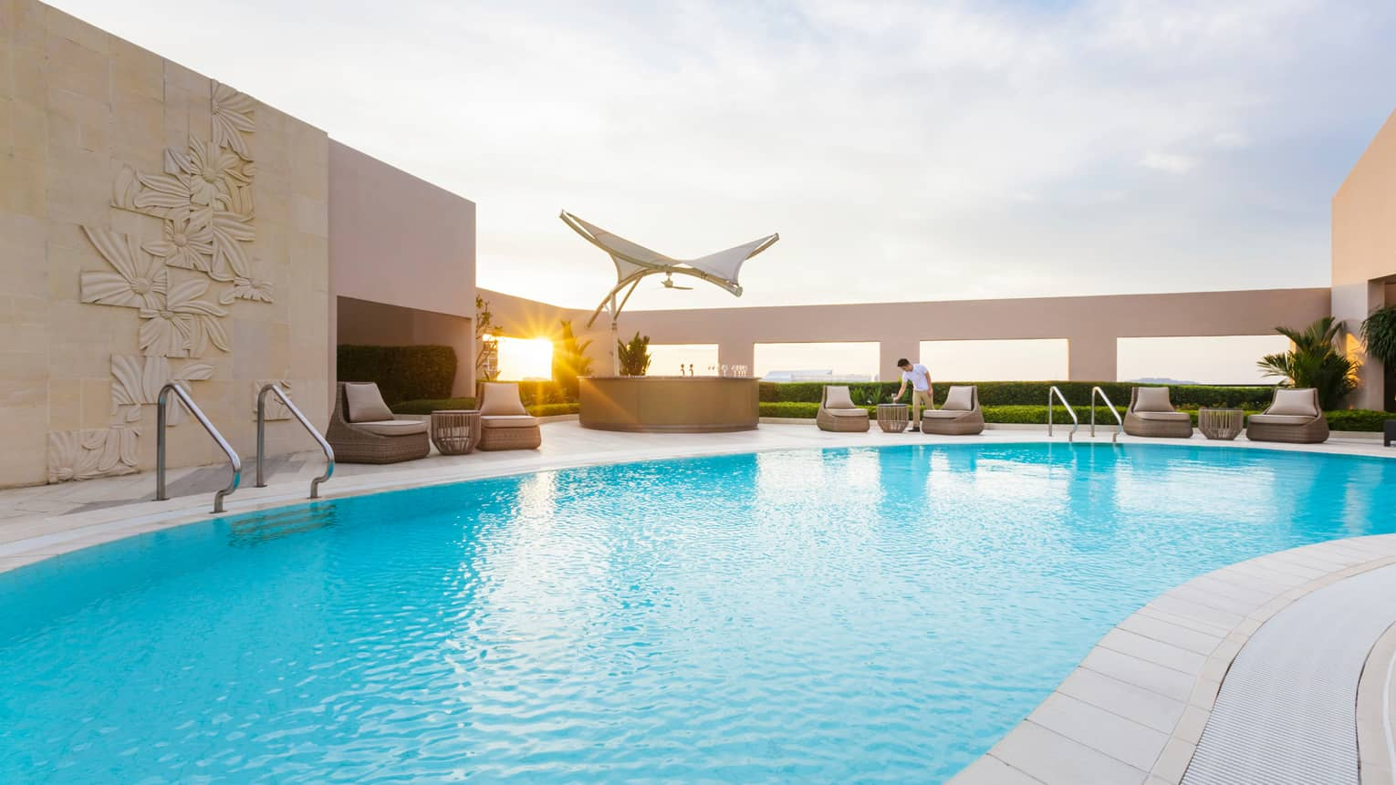 Sun peeks through decorative white cement walls, pillars around outdoor swimming pool