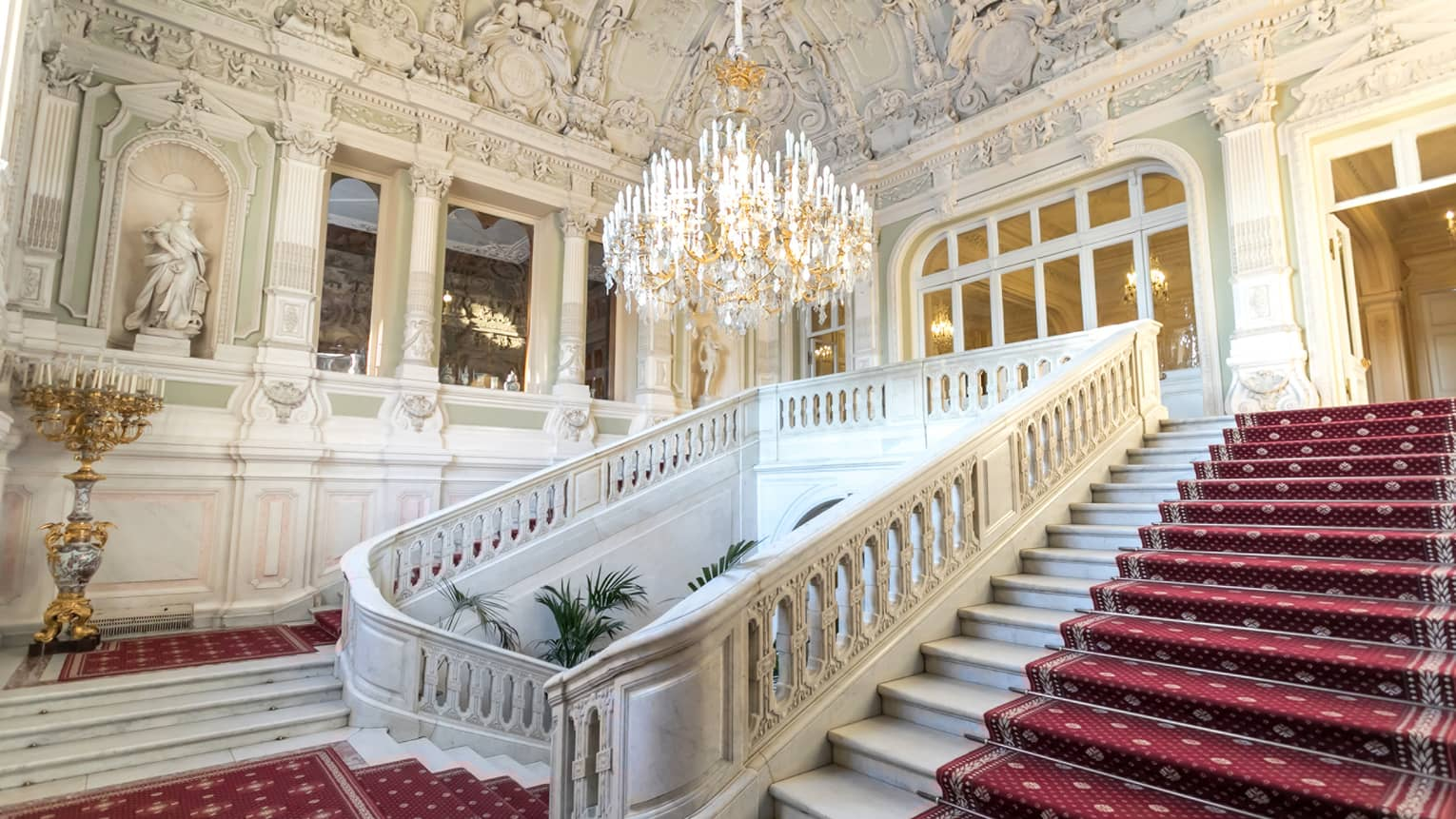 Historic ornate marble stairway with elegant red carpet under large crystal chandelier