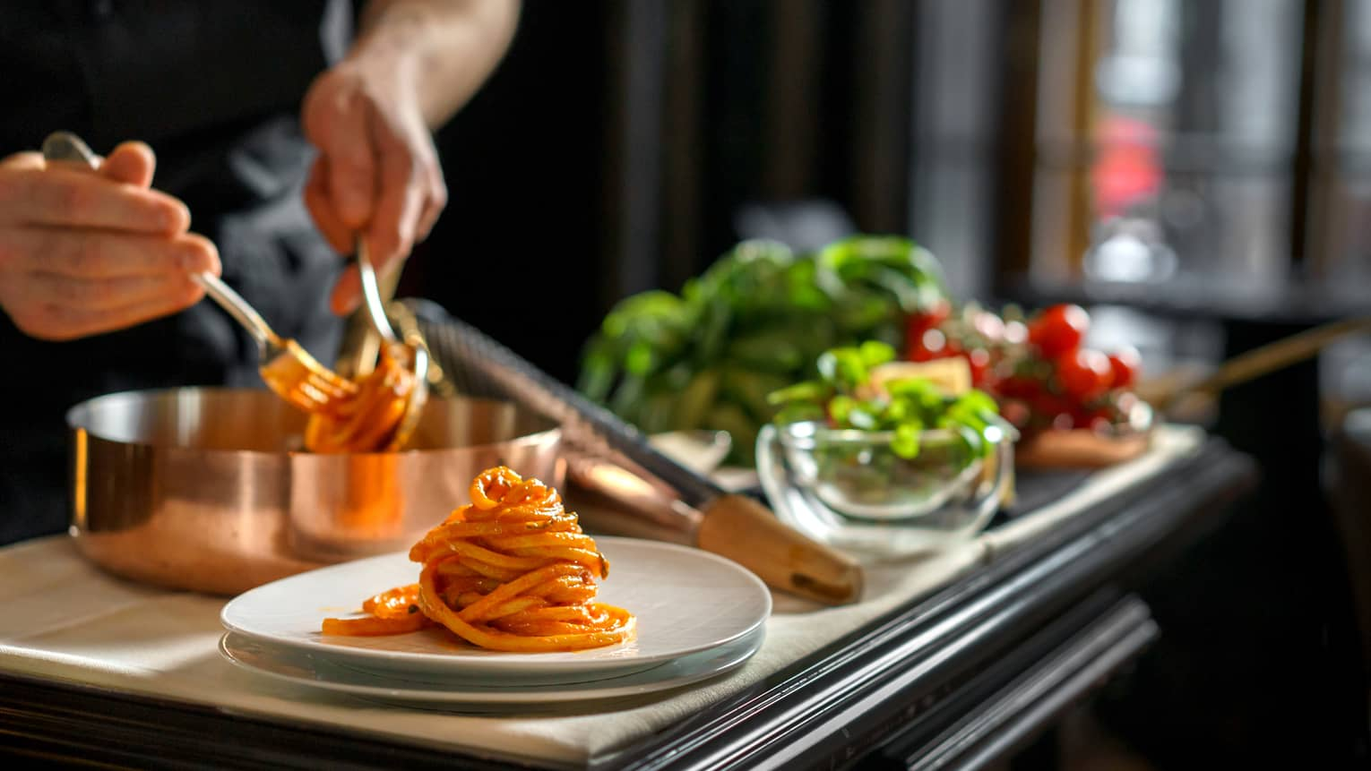 Chef dishes out spaghetti noodles piled on plate next to fresh vegetables